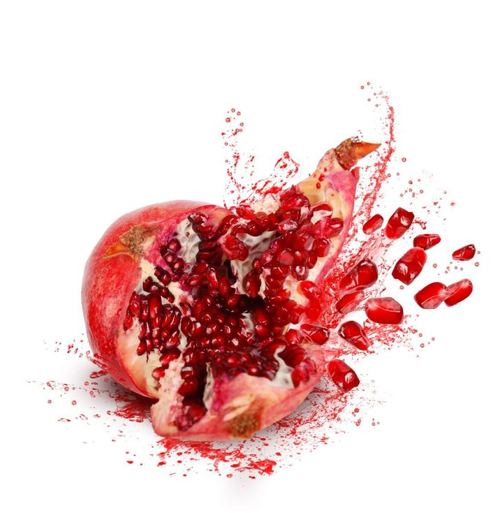 11270117 - falling down ripe pomegranate with cracks and splashes of juice and seeds on white background