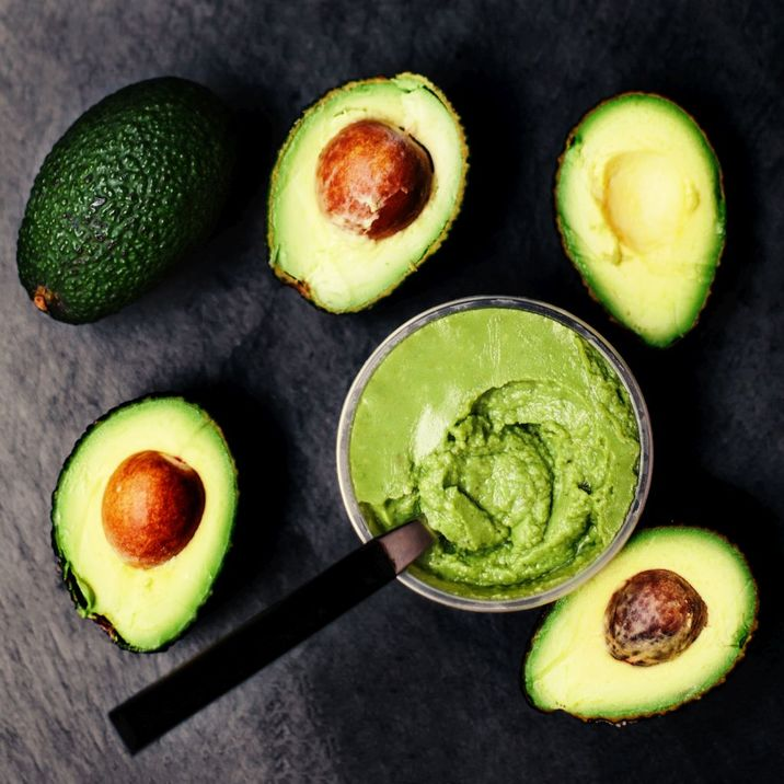 Halved avocados over black background. Top view. Avocado spread. Avocado pasta. Guacamole