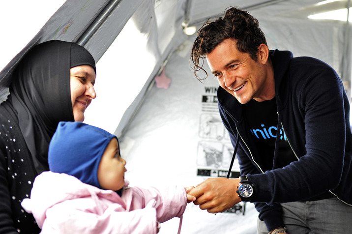 Orlando Bloom, ambassadeur de l'UNICEF portant un tee-shirt UNICEF, salue une femme et une petite fille dans un espace pour les enfants lors de sa rencontre avec des migrants dans un centre d'accueil pour réfugiés et migrants près de la ville Gevgelija en Macédoine à la frontière avec la Grèce le 29 septembre 2015. L'espace pour les enfants du centre, géré par l'UNICEF, est un lieu consacré aux enfants où ils peuvent s'installer, jouer, recevoir de la nourriture et de l'eau, avoir des vêtements chauds, se laver... On 29 September (right) UNICEF Goodwill Ambassador Orlando Bloom greets a child and a woman in a child-friendly space at the refugees and migrants reception centre near the town of Gevgelija, close to the border with Greece. The child-friendly space provides an environment where children have access to a safe place to rest, play and receive food and water, warm clothes, sanitation and the hygiene and protection services that they need through UNICEF-supported services.