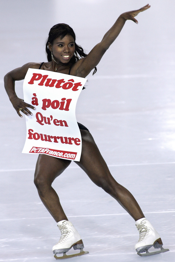 """French figure skating star Surya Bonaly skates for photographers holding a placard that reads """"Rather naked than wearing fur"""", Wednesday, Jan. 31, 2007 at the Asnieres-sur-Seine skating rink, outside Paris. Bonaly supports animal rights group Peta's demand and protests against seal culls in northern Canada. (AP Photo/Jacques Brinon)"""