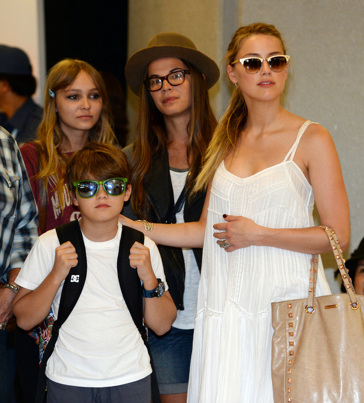 "US actress Amber Heard (R), partner US actor Johnny Depp, his daughter Lily-Rose Melody (back L) and son Jack (front L) watch as the actor is greeted by fans upon arriving at Narita International airport in Narita, Chiba prefecture, northeastern suburb of Tokyo on July 16, 2013. Depp is here to promote his latest Disney Enterprises movie, ""The Lone Ranger"" which will be shown nation wide in Japan from August 2.         AFP PHOTO / TOSHIFUMI KITAMURA"