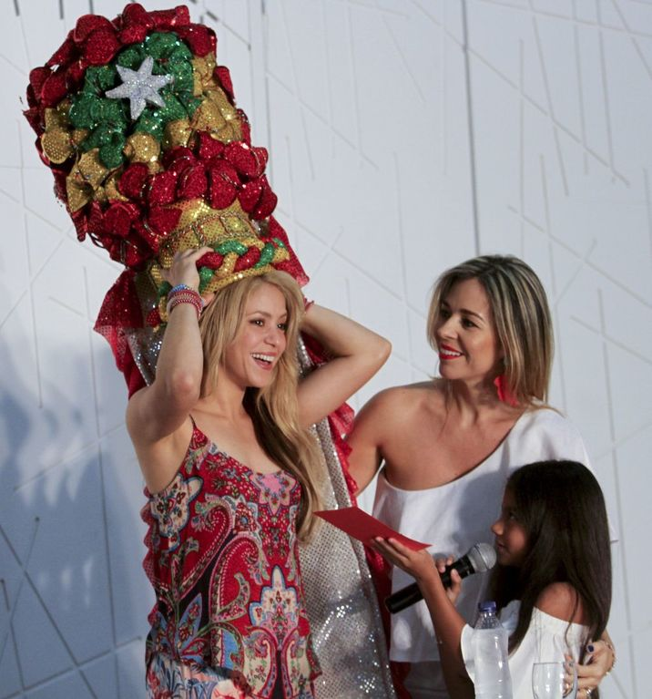 """Colombian singer Shakira receives the Congo's hat of the Barranquilla's Carnival from her fans during a press conference in Barranquilla, Atlantico department, Colombia, on May 21, 2016. Shakira is in the city to record a video for the song """"La Bicicleta"""" (The bicycle) -in which she performs with Colombian singer Carlos Vives. / AFP PHOTO / JOSE TORRES"""