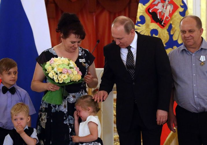 MOSCOW, RUSSIA - JUNE 1: (RUSSIA OUT) Russian President Vladimir Putin attempts to comfort 4-year-old Yana Kleshova while giving an award to the Kleshovs family at the Grand Kremln Palace on June 1, 2016 in Moscow, Russia. Putin marked the International Children's Day and awarded nine big Russian families with the order for activities that promotes the insitution of the familiy and child-rearing. (Photo by Mikhail Svetlov/Getty Images)