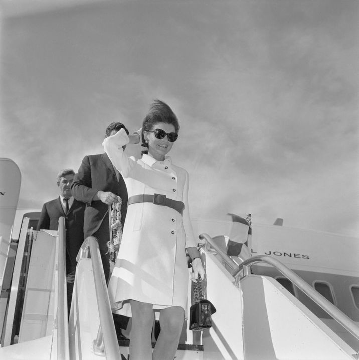 (Original Caption) Mrs. John F. Kennedy, clad in a white dress with fashionable short skirt, smiles as she disembarks in Rome following a 10-day Asian holiday. The former First Lady is expected to spend several days in Rome before returning to the United States.