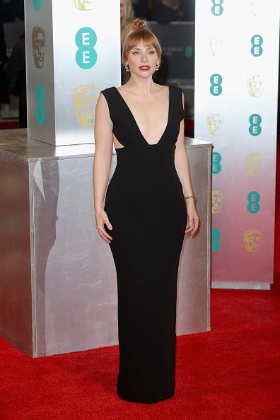 Într-o rochie clasică neagră Solace London.
