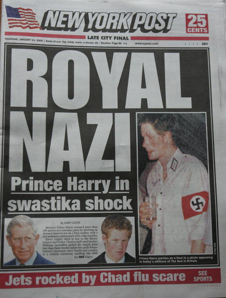 """NEW YORK - JANUARY 13:  A copy of the New York Post front page lies on display featuring a """"Royal Nazi"""" headline January 13, 2005 in New York City. British royal, Prince Harry, reportedly attended a fancy dress party wearing a khaki uniform with an armband emblazoned with a swastika, the emblem of the German WWII Nazi Party.  (Photo by Stephen Chernin/Getty Images)"""