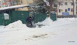Fotografia zilei. Un batran in carucior cu rotile din Buzau se chinuie sa dea zapada la o parte cu lopata