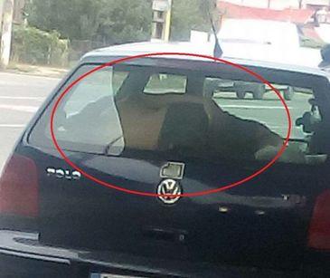 Inconstienta maxima! Copil fotografiat cand doarme intre luneta si bancheta din spate a masinii