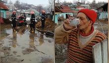 Tatal a sase copii savureaza un pahar de alcool  in timp ce pompierii ii scot apa din gospodaria inundata